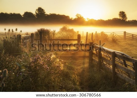 Beautiful sunrise landscape over foggy English countryside with glowing sun