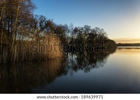 Beautiful sunrise landscape over lake with reflections and jetty
