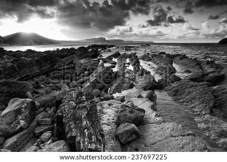 Stock Photo Beautiful sunrise landscape over Mupe Bay on Jurassic Coast in Dorset, England  black and white