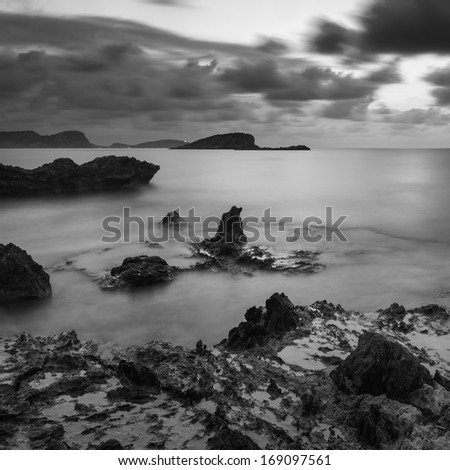 Beautiful sunrise landscape seascape over rocky coastline in Mediterranean Sea in black and white