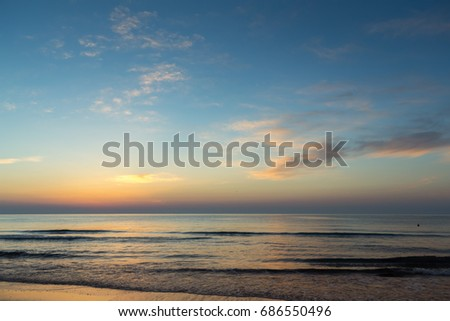 Beautiful sunrise of the Black Sea shot in Mamaia tourist resort in Romania. Vivid colors showing up at the horizon while waves hitting the shore #686550496