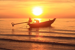 Beautiful sunrise on the beach and silhouette of fishing boat.Fisherman technic.selective focus.