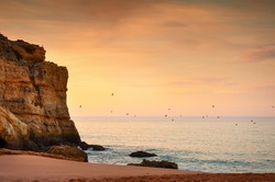 Beautiful sunrise on the beach in Algarve, Portugal. Flock of birds flying over the water. Shore of Atlantic ocean. Beautiful summer seascape, famous travel destination
