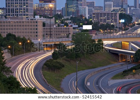 Beautiful sunrise or sunset in Atlanta, Georgia showing city skyline and light streaks from rush hour traffic
