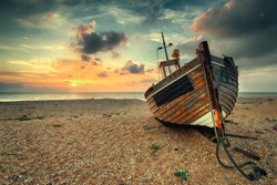 Beautiful sunrise over an old wooden fishing boat on a pebble beach, vintage effect.