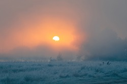 Beautiful sunrise over foggy autumn meadow with hoar frost on the grass. Sun disk rising up over the trees on the river bank. October dawn.