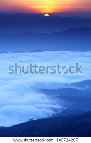 Beautiful sunrise over mountains with morning mist in valley in north at Nan Province of Thailand
