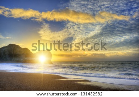 Beautiful sunrise over ocean with rock stack in foreground