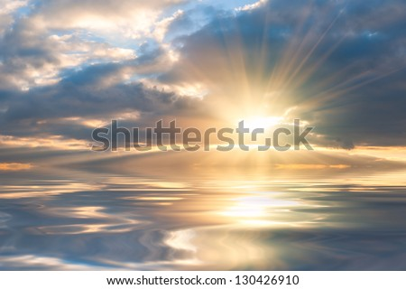Beautiful sunrise over sea with reflection in water, majestic clouds in the sky