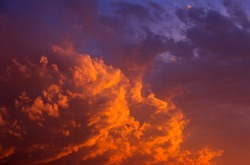 Beautiful sunrise, sunset colors on the underside of a dense, but fragmented cloud cover. The colors range from yellows and light orange to red and magenta.