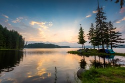 Beautiful sunrise view with a mountain lake surrounded by conifers. Shiroka Polyana dam in Rhodopi Mountains, Bulgaria.