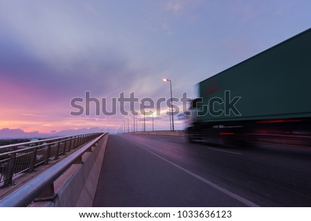 Beautiful sunrise with blurred truck transportation on the road