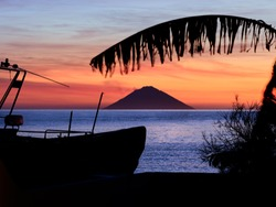 Beautiful sunrise withe the Stromboli volcano seen from the Salina island in the Aeolian islands, Sicily, Italy