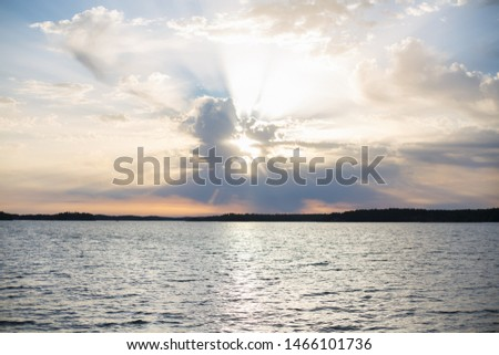 Beautiful sunset above a river or sea. Fantastic sky with sun rays. Sun rays from clouds.