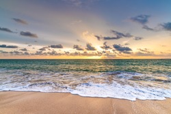 Beautiful sunset above sea or ocean. Vibrant and soft colors, magic light. Small clouds on the sky, reflection of sun in the water and sand on beach. Concept of romantic time on vacation in tropical.