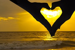 Beautiful sunset above the sea, and hands whit love signal