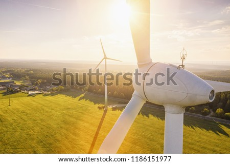 Beautiful sunset above the windmills on the field