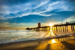 Beautiful Sunset and Clouds flowing through the Huntington Beach pier and onto the beach