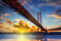 Beautiful sunset and dramatic sky above the Red Bridge , Lisbon, Portugal in autumn time at evening. Vintage style travel background