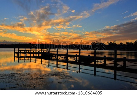 Beautiful sunset and mirrored reflections against a timber jetty silhouette #1310664605