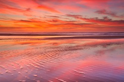 Beautiful sunset and reflections on the beach at low tide.