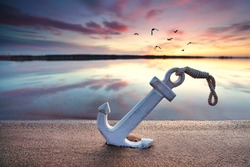 beautiful sunset at the beach, wooden anchor in the sand at the coast