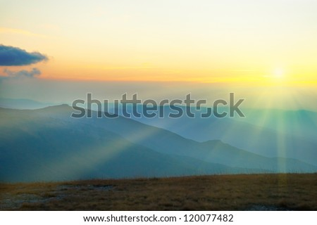 Beautiful sunset at the mountains. Colorful landscape with sun and blue sky