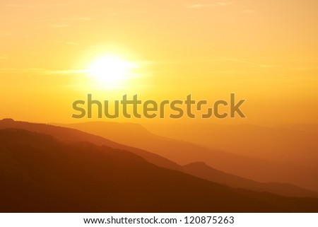 Beautiful sunset at the mountains. Colorful landscape with sun and orange sky