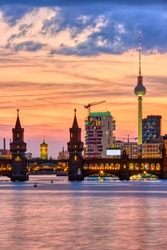 Beautiful sunset at the Oberbaum Bridge in Berlin with the famous Television Tower in the back