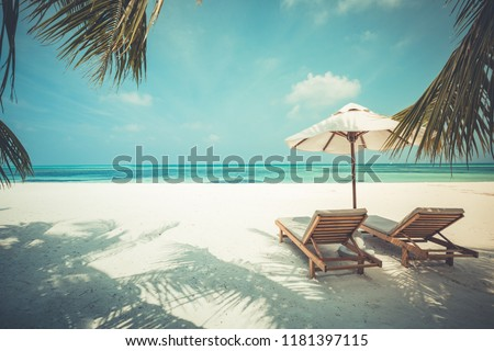Beautiful sunset beach scene. Chairs on the sandy beach near the sea. Summer holiday and vacation concept for tourism. Inspirational tropical landscape