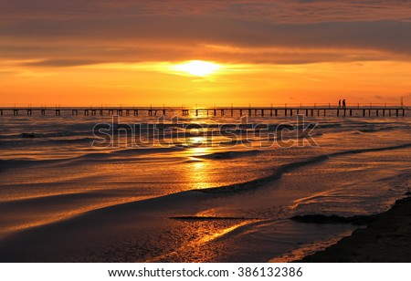 Beautiful sunset & black sea landscape. Sunny sea sunset view & jetty with people silhouette landscape. Unbelievable sea sunset in evening. Gold sea sunset with smooth waves small bridge & orange sky