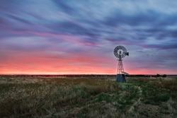 Beautiful sunset falling behind a windmill.