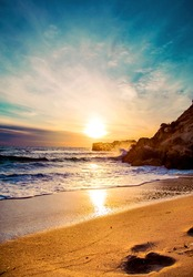 Beautiful sunset in a tipical beach from Ibiza with warm colours, clear water and a footprint on the sand