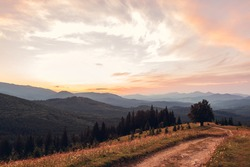 Beautiful sunset in Carpathian mountains. Summer ukrainian landscape. Dusky sky above wild nature with path