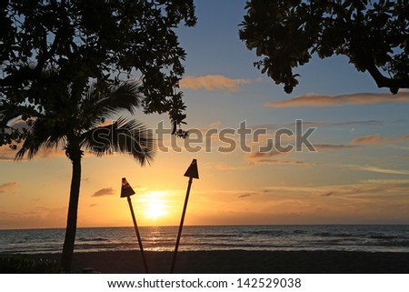 Beautiful sunset in Hawaii with Tiki Torches burning