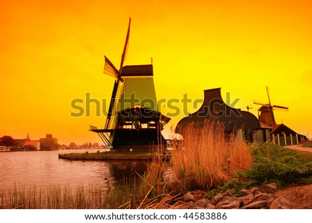 Beautiful sunset in Holland with a view at pasture with wind mills. Zaandam