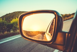 Beautiful sunset in sideview car mirror on mountain road