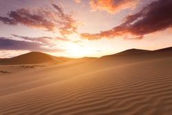Beautiful sunset in the Sahara desert. Sand dunes at sunset