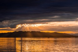 Beautiful sunset in the sea with the light comming through the clouds