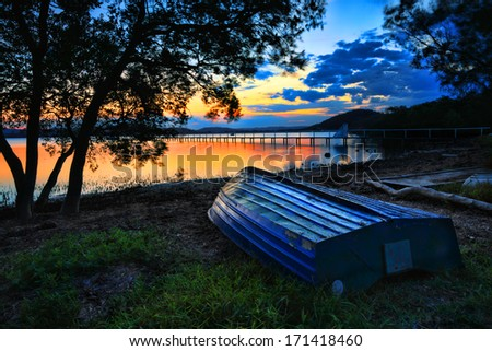 Beautiful sunset landscape with  blue weathered upturned boat at shoreline at low tide.  This pretty spot is Kincumber, Australia.  Please note long exposure, t some motion in trees due to breeze