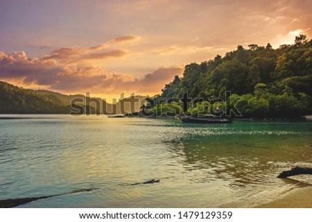 beautiful sunset on mai ngam beach mu ko surin national park with sunlight hits the mountain and twilight sky