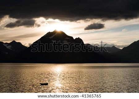 beautiful sunset on mountain lake with small fishing boat and black clouds - stock photo