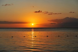 Beautiful sunset on ocean cost of tropical island. Magical and emotional sunset moment. Wonderful scenery of colourful sky and ocean.