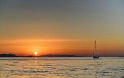 Beautiful sunset on ocean cost of tropical island with single boat in foreground. Magical and wonderful sunset. Emotional moment.