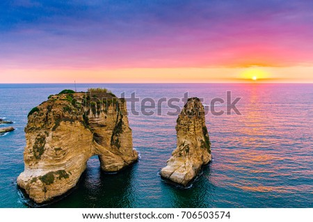 Beautiful sunset on Raouche, Pigeons' Rock. In Beirut, Lebanon.Sun and Stones are reflected in water.dense clouds in the sky. #706503574