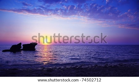Beautiful sunset on the beach, seascape with calm ocean and rocks in the blue water
