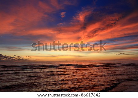 Beautiful Sunset on the beach with dramatic orange and dark shade of blue sky in the evening.