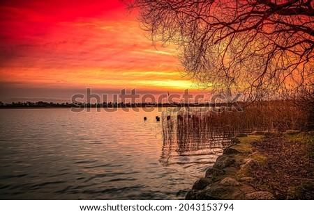Beautiful sunset on the river bank. Sunset river landscape. River at sunset. Red sunset river