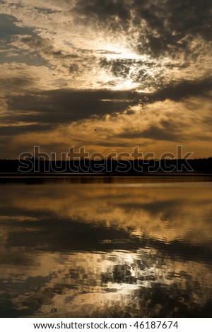 Beautiful sunset over a reservoir with reflections in the water.