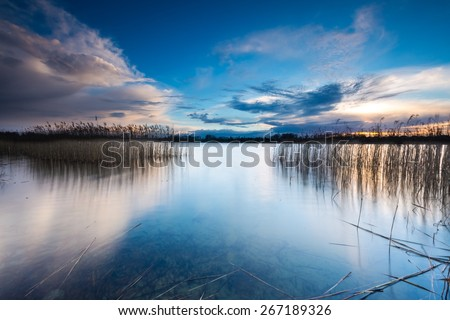 Beautiful sunset over calm lake in Mazury lake district. After sunset sky reflecting in water, calm vibrant landscape. #267189326